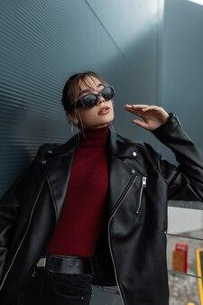 Cool jonge model vrouw met vintage zonnebril in modieuze zwarte leren jas met zwarte jeans en bordeauxrode trui poseren in de buurt van een modern metalen gebouw in de stad