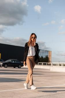 Cool jonge vrouw in stijlvolle zwarte jas in vintage broek in fashion zonnebril in top wandelingen op asfalt op achtergrond blauwe hemel op zonnige heldere zomerdag. modieuze meisjesreis in stadsparkeerplaats.