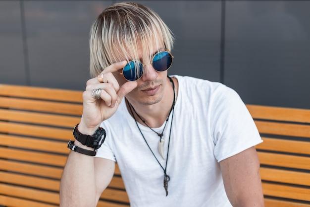 Cool jongeman blond in een trendy wit t-shirt met vintage amuletten om de nek zit op een gele houten bank en zet stijlvolle blauwe zonnebril recht. knappe jongen is aan het ontspannen in de stad.