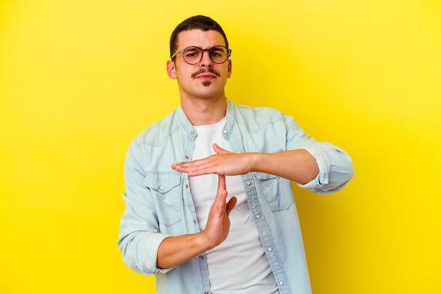 Cool jongeman geïsoleerd op gele muur met een time-out gebaar