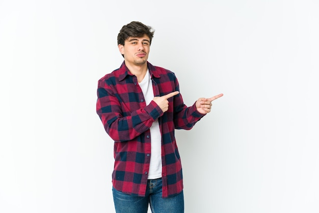Cool jongeman geschokt wijzend met wijsvingers naar een kopie ruimte.