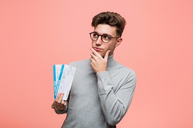 Cool jongeman met een kaartje opzij kijken met twijfelachtige en sceptische uitdrukking.