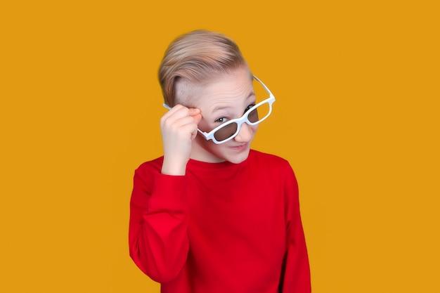 Cool kind in rode kleding en bril met emoties van verrassing op een gele achtergrond