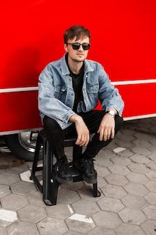 Cool knappe jongeman in een modieus spijkerjack in trendy zwarte broek in vintage zonnebril zittend op een ladder in de buurt van een modern rood busje in de stad. stijlvolle aantrekkelijke kerel hipster buitenshuis