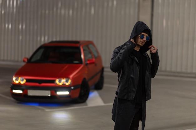 Cool knappe modieuze man met zonnebril in stijlvolle kleding met een leren jas en een hoodie poseert in de buurt van een rode tuning auto op een parkeerplaats in een nachtstad