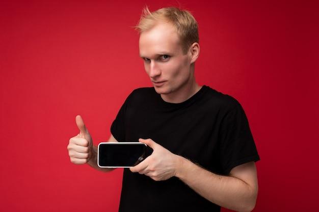 Cool knappe serieuze blonde jongeman met zwarte tshirt staande geïsoleerd op rode achtergrond met