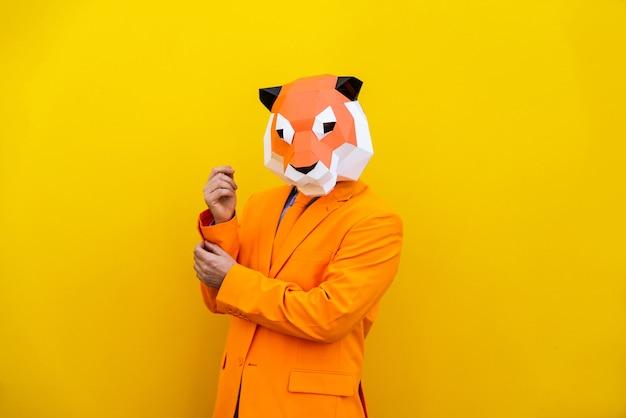 Cool man met 3d origami masker met stijlvolle gekleurde kleding - creatief concept voor reclame, dierenkop masker grappige dingen doen op kleurrijke achtergrond