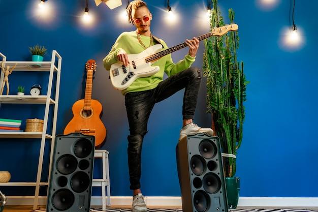 Cool man met dreadlocks oefenen thuis gitaar spelen