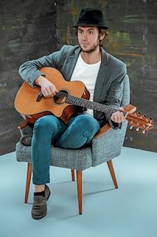 Cool man met hoed gitaarspelen op grijs