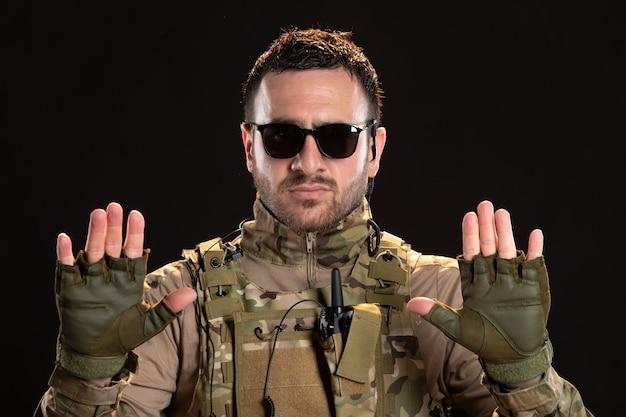 Cool mannelijke soldaat in camouflage overgave op zwarte muur