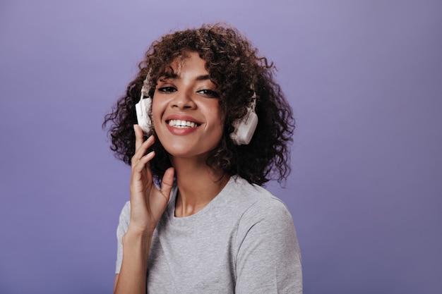 Cool meisje in grijze top lacht en luistert naar muziek op paarse muur