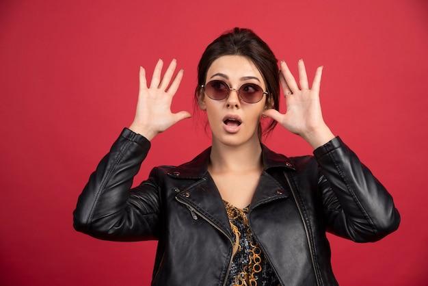 Cool meisje in zwart lederen jas steekt handen op en geeft het op.