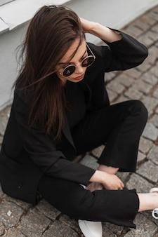 Cool moderne jonge vrouw in zonnebril in modieuze zwarte vrijetijdskleding rechtzetten haar in de buurt van vintage houten gebouw op straat in de stad. amerikaanse trendy meisje mannequin rust op stenen tegel.