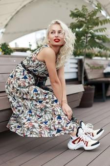 Cool modieus mooi model vrouw in een stijlvolle vintage jurk met mode schoenen zit op een houten bankje