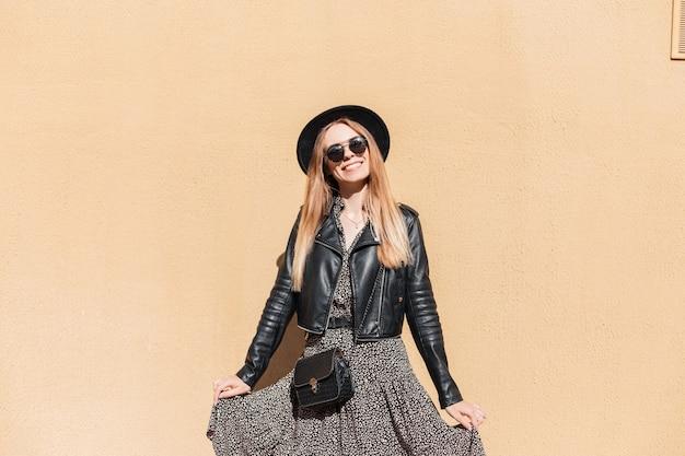 Cool mooie vrouw met glimlach in fashion look met leren jas, vintage jurk, zonnebril, hoed en stijlvolle handtas poses in de buurt van een gele muur buitenshuis