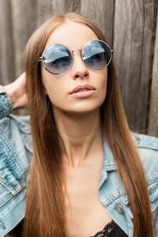 Cool portret van een jonge vrouw met een modieuze blauwe zonnebril in een stijlvol spijkerjack buitenshuis