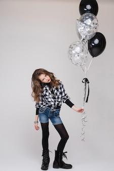 Cool pre-tiener meisje met stenen bord. ze vertoont een rock-'n-roll- of hoornteken, gebaart en pruilt haar lippen met twee luchtballonnen.