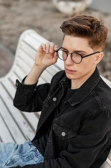 Cool serieuze jongeman in modieuze denim kleding in stijlvolle bril rustend op houten bankje op straat. portret knappe amerikaanse man mannequin buitenshuis. jeugd stijl. casual herenkleding.