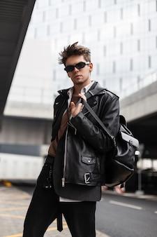 Cool stijlvol jong mannelijk model in vintage zonnebril in een modieuze leren jas in spijkerbroek met een vintage rugzak poseren in de buurt van een modern gebouw op straat. aantrekkelijke hipster kerel in de stad.