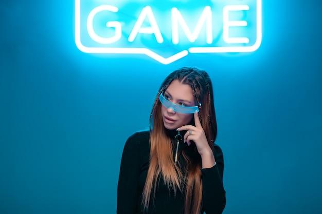 Cool stijlvol meisje met een modieus kapsel en een stijlvolle bril met een groot glas vormt op een heldere neon achtergrond.