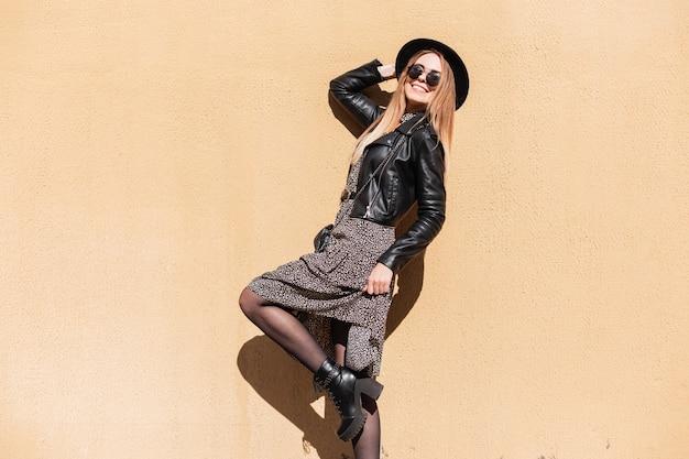 Cool stijlvolle hipster grappige vrouw met glimlach in fashion zonnebril met vintage jurk, leren jas, hoed met mode schoenen poseren in de buurt van beige muur in zonlicht