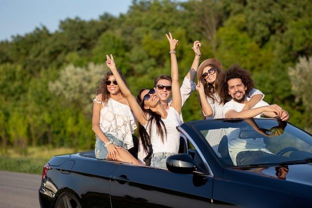 Cool stijlvolle jonge donkerharige meisjes en jongens in zonnebrillen glimlachen in een zwarte cabriolet op de weg met hun handen omhoog op een zonnige dag. .
