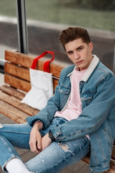 Cool stijlvolle jongeman in trendy blauwe jeugd casual jeans kleding zittend op een houten bankje en wachten op openbaar vervoer. europese man in trendy kleding bij glazen bushalte. zomer nieuwe collectie.