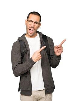 Cool student wijzend met zijn vingers