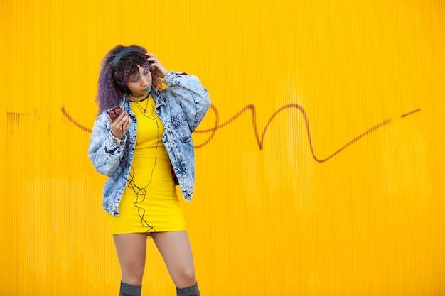 Cool tiener met afro haar luisteren naar muziek op een gele muur