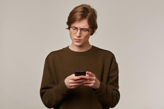 Cool uitziende mannelijke, knappe man met blond haar. bruine trui en bril dragen.