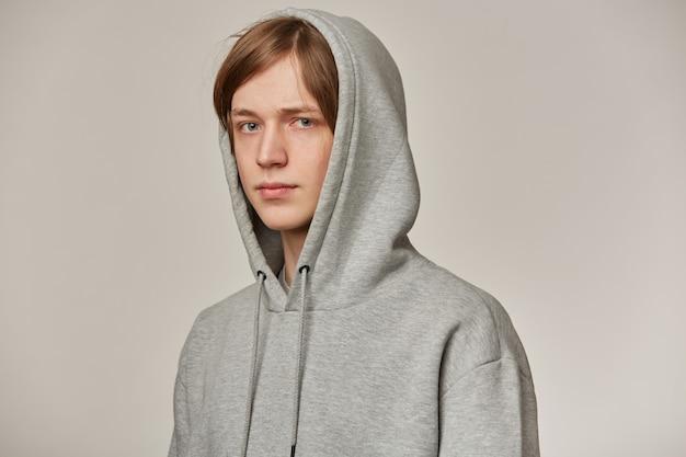 Cool uitziende mannelijke, knappe man met blond haar. ik draag een grijze hoodie en zet een capuchon op. mensen en emotie concept. kijken naar serieuze geïsoleerde over grijze muur
