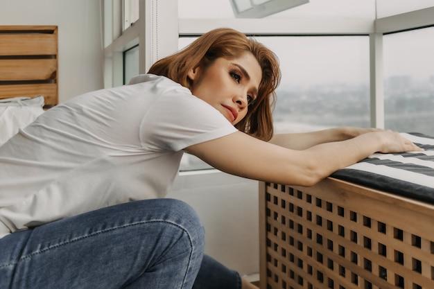 Cool uitziende vrouw rust en kijkt naar het uitzicht vanuit haar appartement