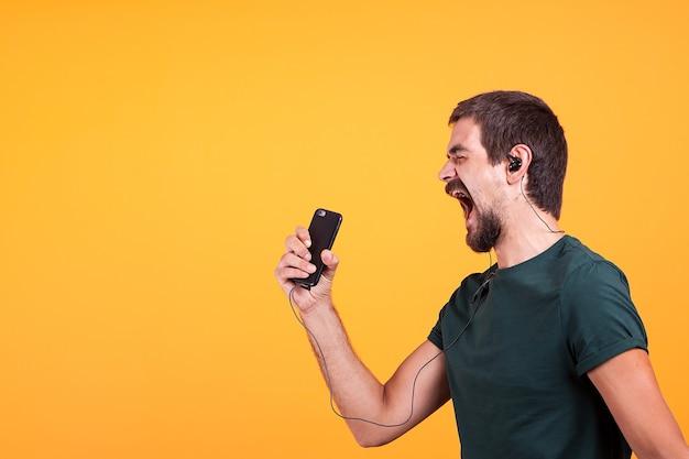 Cool vrolijke jongeman luisteren en genieten van muziek in zijn koptelefoon terwijl hij zijn smartphone in handen houdt. moderne technologie en apparaat