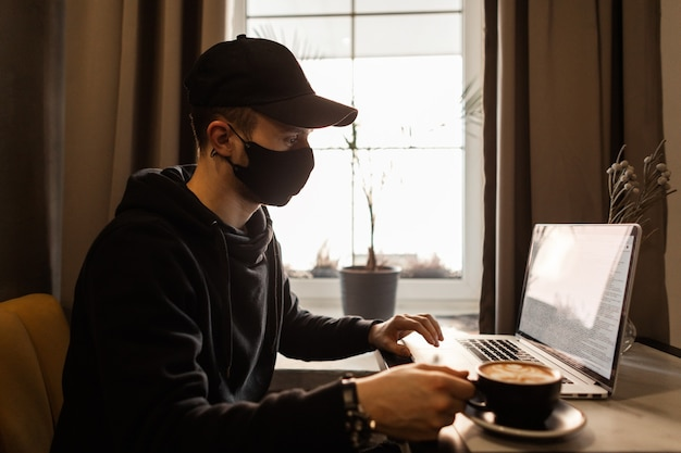Cool zakenman man met een zwart medisch masker in zwarte modieuze kleding met een pet en een hoodie zit in een café koffie te drinken en op een laptop te werken. coronavirus en pandemisch concept