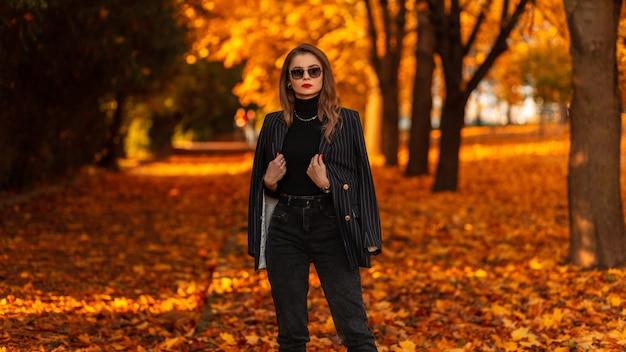 Cool zakenvrouwenmodel met stijlvolle zonnebril in modieuze zwarte pakkleren met modieuze blazerwandelingen in het herfstpark met oranje gebladerte
