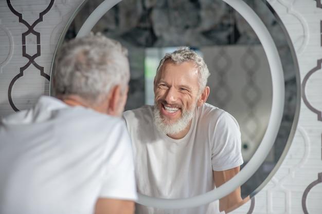 Cool zijn. een glimlachende grijsharige man die in de spiegel kijkt