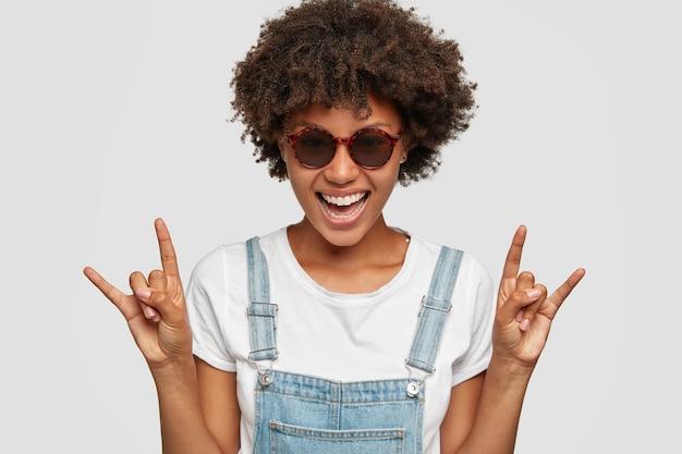 Coole afrikaanse vrouw die muziekster is, maakt rock-symbool met omhoog handen