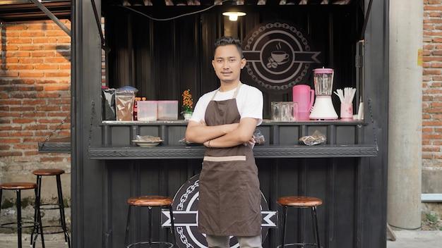 Coole aziatische barista met capuchon in een winkel met containerthema