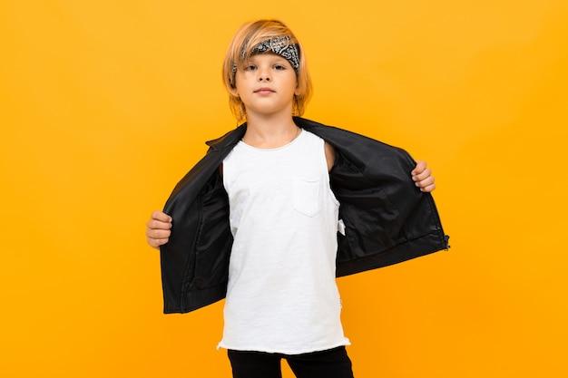 Coole blonde jongen in een zwart leren jas en wit t-shirt met mock up met een bandana op geel