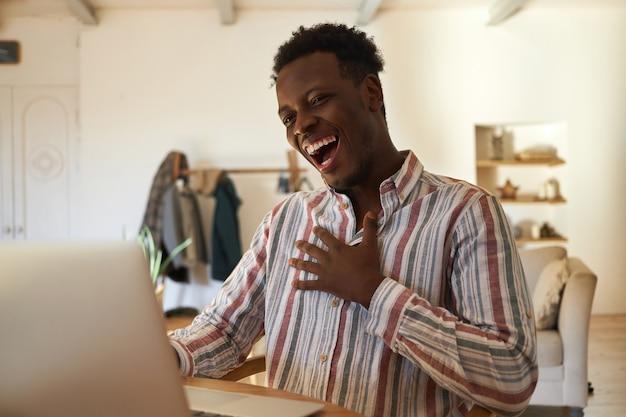 Coole charismatische jonge donkere man ontspannen thuis met behulp van laptop tijdens het surfen op internet, komedie kijken of opstaan show online, lachen om grap, hand op zijn borst houden.