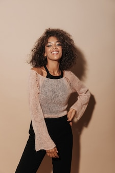 Coole dame met donkerbruin haar en charmante make-up in roze trui, zwarte top en moderne broek die in de camera kijkt en lacht op geïsoleerde muur..