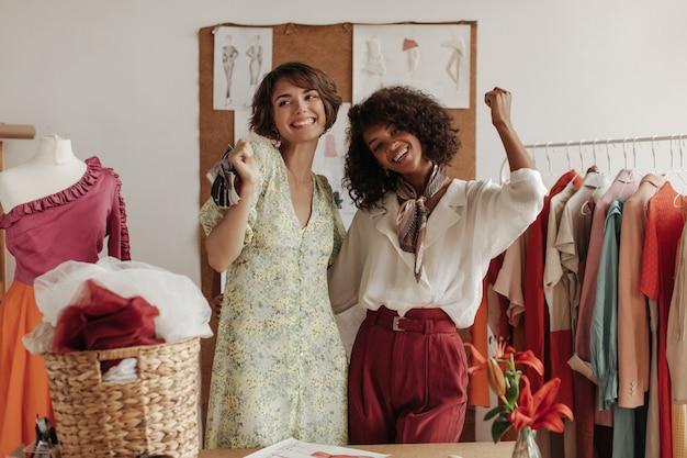 Coole jonge dames poseren in de buurt van etalagepop in kantoor van modeontwerper