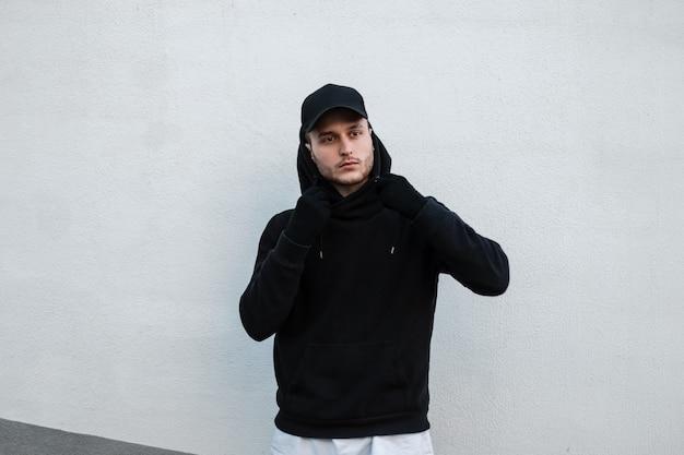 Coole jonge knappe hipster-man in een stijlvolle zwarte pet met een modieuze zwarte hoodie staat in de buurt van een witte muur op straat