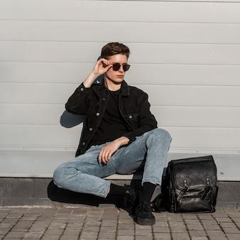 Coole jonge man in modieuze zwarte denim herenkleding met leren rugzak in schoenen