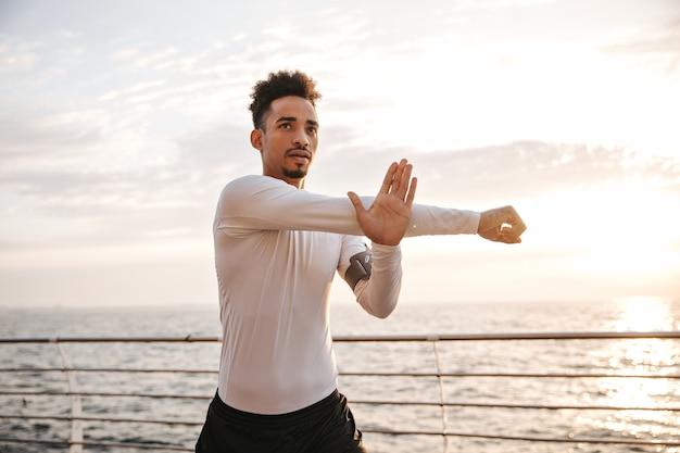 Coole jonge man met donkere huidskleur in wit t-shirt met lange mouwen en zwarte korte broek strekt zich uit en traint in de buurt van zee