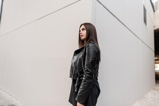 Coole jonge, mooie stijlvolle hipster-vrouw in een zwart leren jasje en jurk in de buurt van een grijze moderne muur op straat