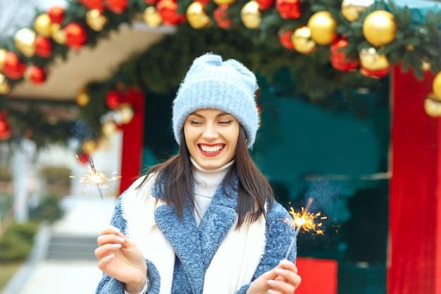 Coole jonge vrouw draagt blauwe jas en geniet van vakantie met bengaalse lichten