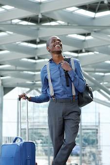 Coole jonge zakenman glimlachend op het station met bagage