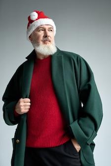 Coole man van middelbare leeftijd met kerstmuts met een stijlvolle outfit die wegkijkt en zijn jas aanpast