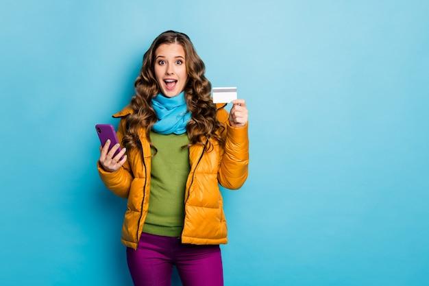 Coole manier van kopen. foto van mooie dame met telefoon die online betaling maakt gebruik plastic creditcard draagt gele overjas sjaal broek jumper geïsoleerde blauwe kleur muur